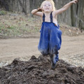 Child jumping in a pile of dirt.