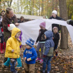 Tinkergarten leader Marissa Northam uses a sheet to create a tunnel for the children in her class in Terre Haute, Ind.