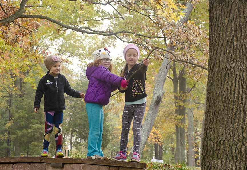 Three girls pretend to have found a bear in a tree.