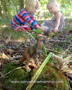 Playing with toy dinosaurs outside.