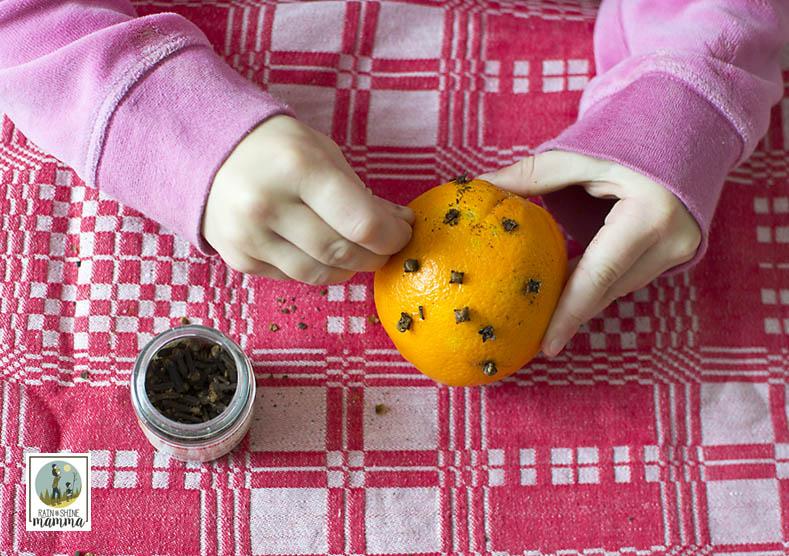 How to Make Pomander Oranges. Push the cloves into the orange. Rain or Shine Mamma.